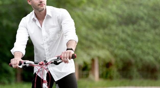 Elegante volwassen mannelijke fietsten buitenshuis