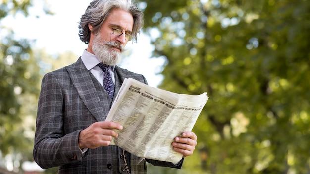 Elegante volwassen mannelijke lezing krant