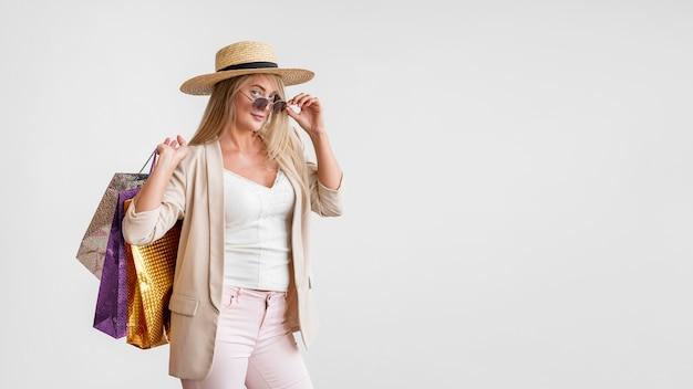 Elegante volwassen vrouw met boodschappentassen met kopie ruimte