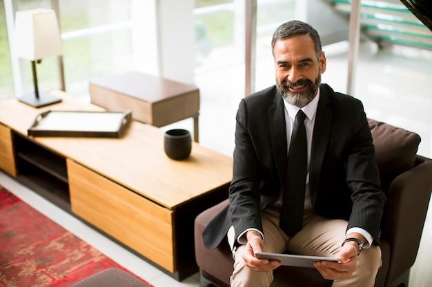 Elegante volwassen zakenman met behulp van multitasking digitale tablet van verschillende media