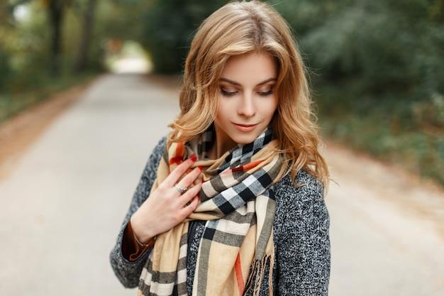 Elegante vrij lieve jonge vrouw met blond haar in een vintage grijze jas met een stijlvolle beige warme sjaal staande op de weg in het park