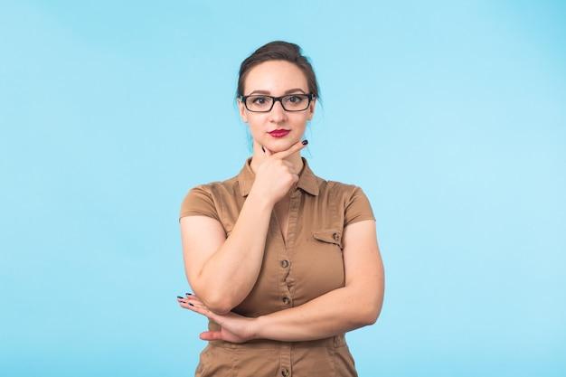 Elegante vrolijke brunette in brillen glimlachend in de camera op blauwe achtergrond met kopieerruimte