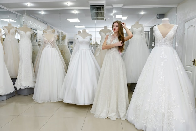 Elegante vrolijke dame in bruidsjurk die in de trouwsalon staat