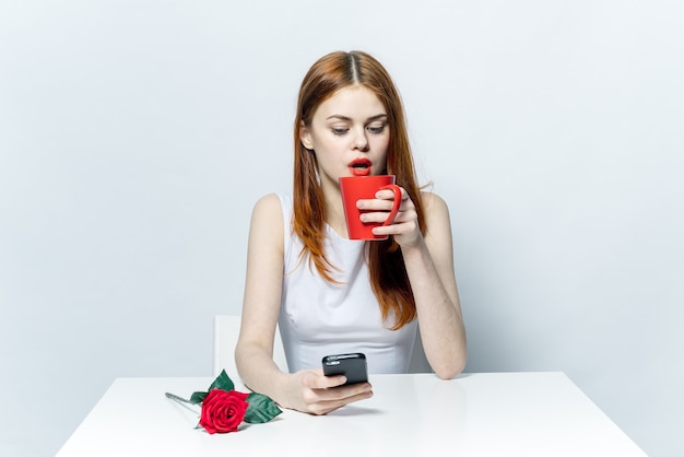 Elegante vrouw aan tafel met een telefoon in haar handen een kopje koffie chatten
