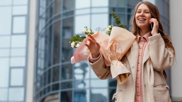 Elegante vrouw boeket bloemen buiten houden en praten aan de telefoon