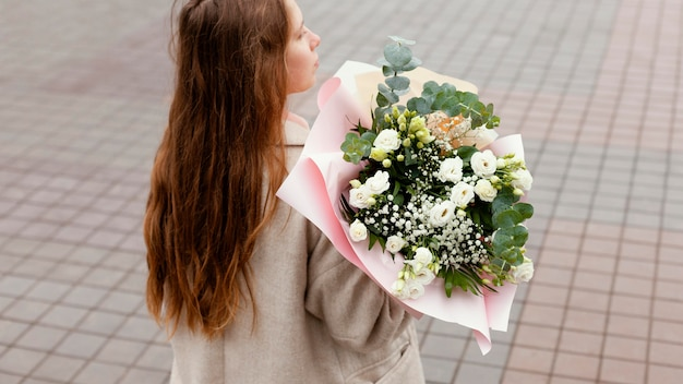 Elegante vrouw buiten bedrijf boeket bloemen