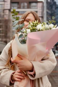 Elegante vrouw buitenshuis ruikende boeket bloemen