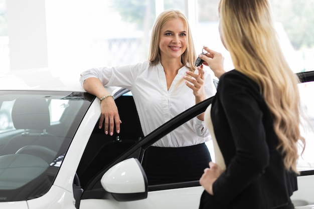 Elegante vrouw die de autosleutels in autotoonzaal ontvangt