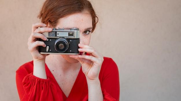 Elegante vrouw die een uitstekende camera met behulp van