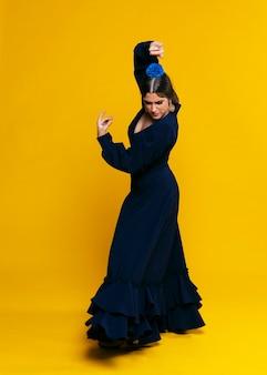 Elegante vrouw die floreo met oranje achtergrond uitvoert