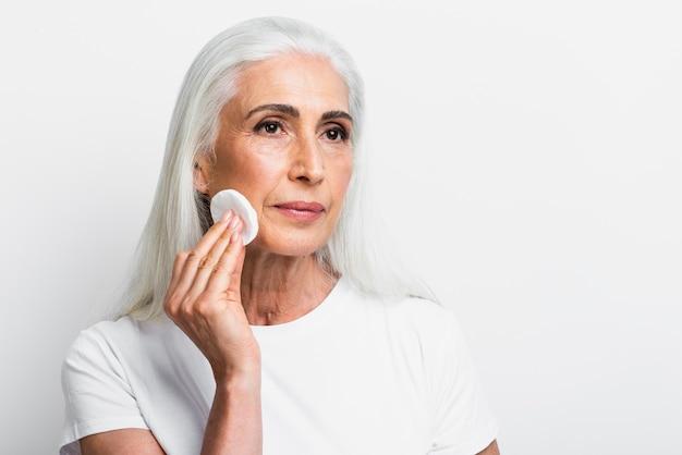 Elegante vrouw die haar gezicht schoonmaakt