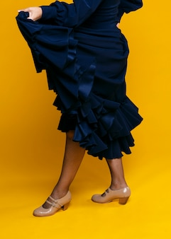 Elegante vrouw die kleding met oranje achtergrond opheft