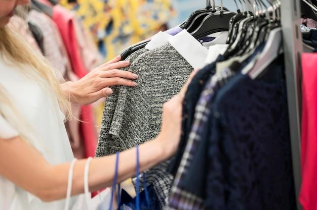 Elegante vrouw die kledingssectie controleren