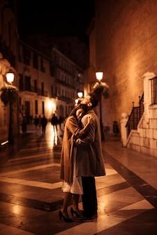 Elegante vrouw die met de jonge mens op promenade in avond koestert