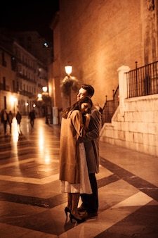 Elegante vrouw die met jonge man op promenade bij nacht omhelzen
