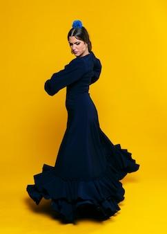 Elegante vrouw die neer met oranje achtergrond kijkt