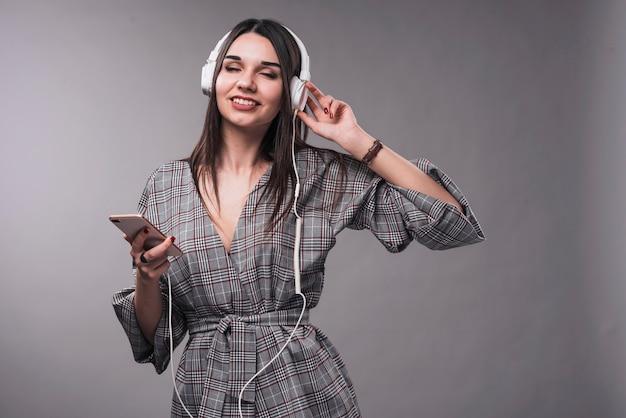 Elegante vrouw die van muziek met gesloten ogen geniet
