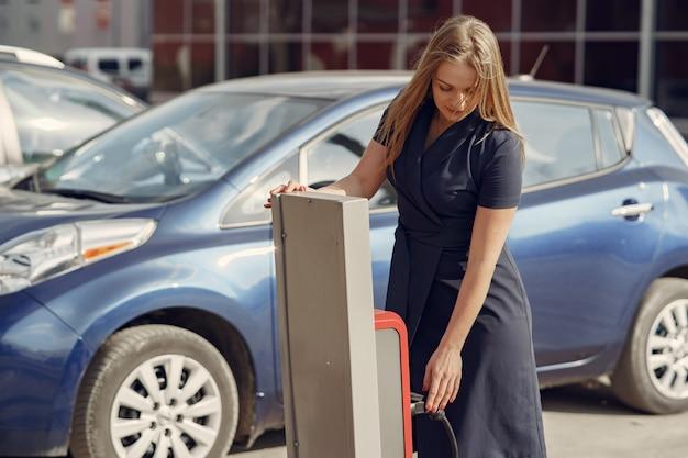 Elegante vrouw die zich op een benzinestation bevindt