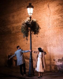 Elegante vrouw en jonge man wervelende in de buurt van verlichte straat lamp