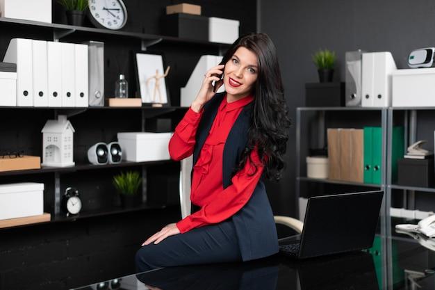 Elegante vrouw ging zitten op tafel met laptop in het kantoor en praten over de telefoon