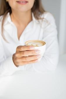 Elegante vrouw houdt kopje cappuccino koffie