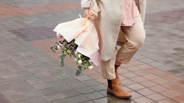 Elegante vrouw in de stad met boeket bloemen