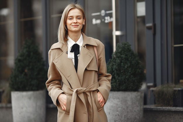 Elegante vrouw in een bruine jas in een lente stad
