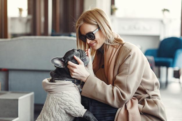 Elegante vrouw in een bruine jas met zwarte bulldog