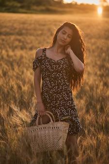 Elegante vrouw in een jurk met mand in het tarweveld bij zonsondergang.