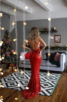 Elegante vrouw in een lange luxe rode jurk tegen de achtergrond van een kerstboom in een interieur