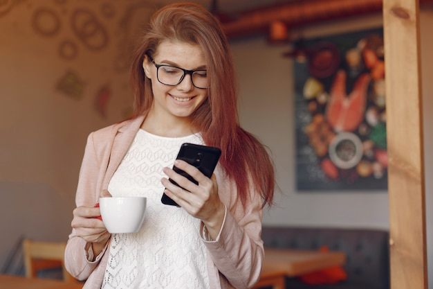 Elegante vrouw in een roze jas tijd doorbrengen in een café