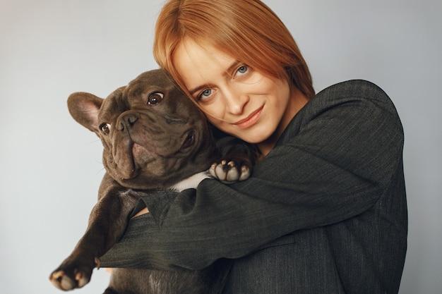 Elegante vrouw in een zwart pak met zwarte bulldog
