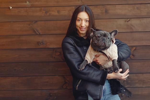 Elegante vrouw in een zwarte jas met zwarte bulldog