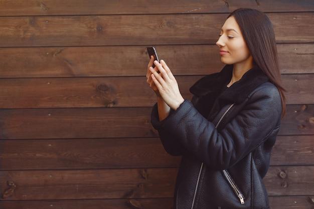Elegante vrouw in een zwarte jas staande op een bruine muur