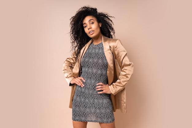 Elegante vrouw in gouden zijden jaket en glanzende sexy jurk met perfect tan lichaam poseren over beige muur. hoge hakken. verbazingwekkende golvende haren.