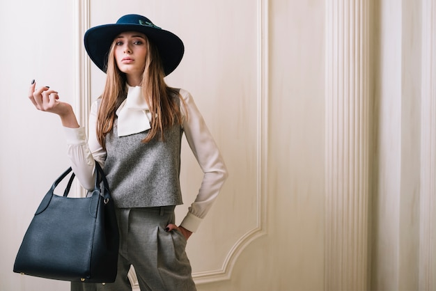 Elegante vrouw in kostuum en hoed met handtas in de kamer