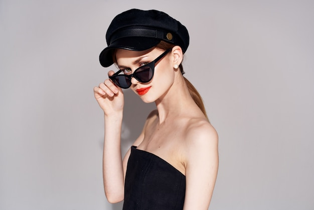 Elegante vrouw in modieuze luxekleding van zonnebril rode lippen