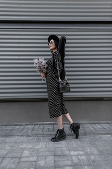 Elegante vrouw in modieuze zwarte kleding uit nieuwe collectie in hoed in zonnebril met tas met boeket verse lila bloemen staat in de buurt van grijze metalen muur in de stad. mode meisje in trendy zwarte outfit.