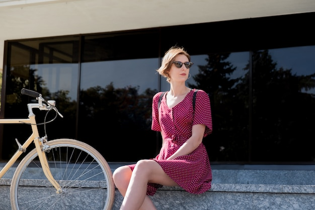 Elegante vrouw in polka dot jurk zittend in de buurt van een retro fiets in stedelijk gebied. mooie jonge vrouw poseren in de buurt van een vintage fiets buitenshuis