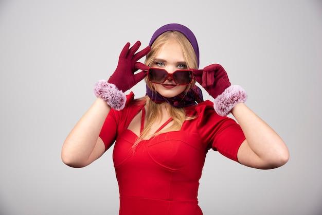 Elegante vrouw in rode jurk met haar bril.