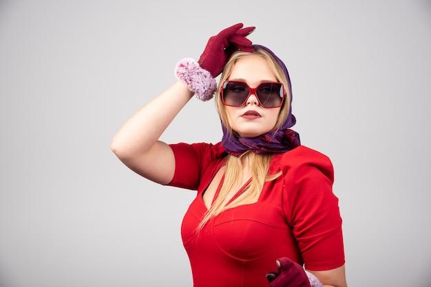 Elegante vrouw in rode jurk poseren voor de camera.