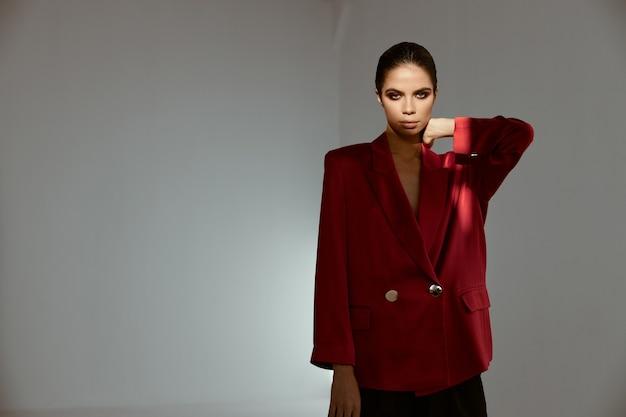 Elegante vrouw in rood de make-up donkerbruin kostuum van de blazeravond