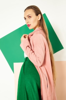 Elegante vrouw in stijlvolle kleurrijke slijtage in studio met witte achtergrond