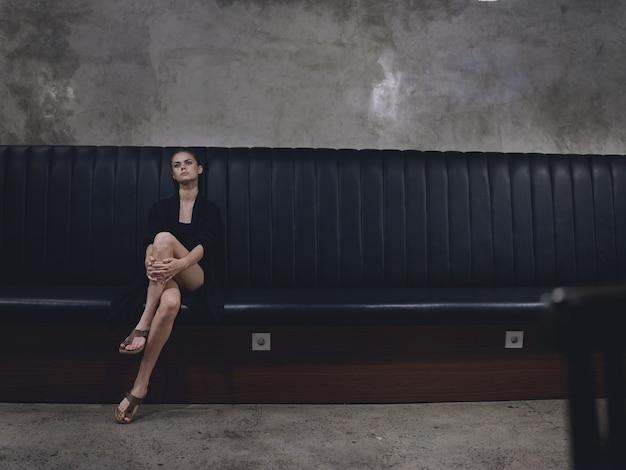 Elegante vrouw in trendy kleding zittend op de bank binnenshuis met benen gekruist in volle lengte