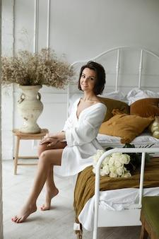 Elegante vrouw in witte jurk vormt en zit op de bank