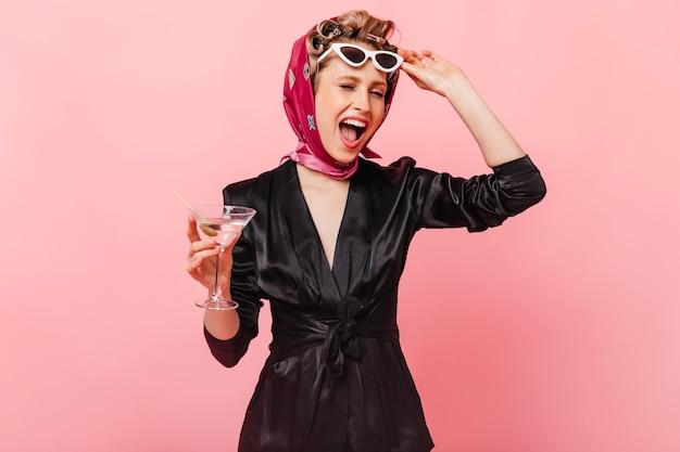 Elegante vrouw in zijden jurk en sjaal neemt haar bril af, knipoogt en poseert met martini op roze muur