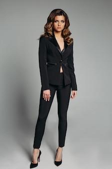 Elegante vrouw in zwart pak en hoge hakken.