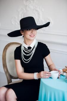 Elegante vrouw in zwarte jurk met een hoed zittend op een stoel
