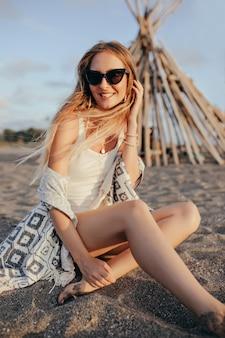 Elegante vrouw in zwarte zonnebril zittend op het strand bij zonsondergang