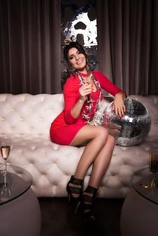 Elegante vrouw met champagnefluit zittend op de bank